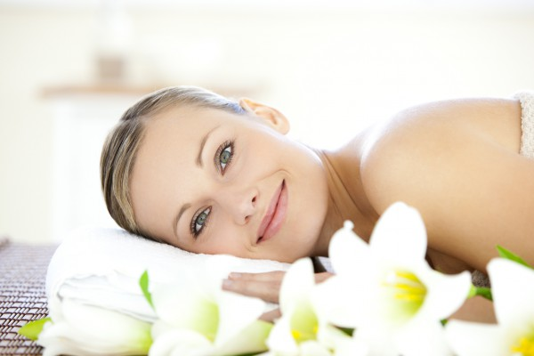 Charming woman lying on a massage table looking at the camera in a spa center