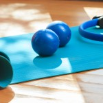 Pilates equipment. Exercise mats and magic ring on wooden floor