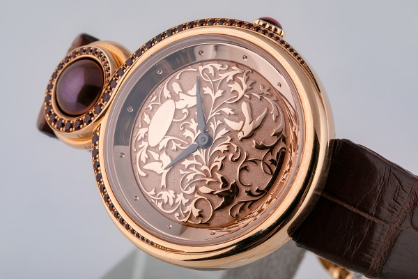 Female rose gold wristwatch with light pink dial with a pattern, black clockwise, on brown leather strap on white background.