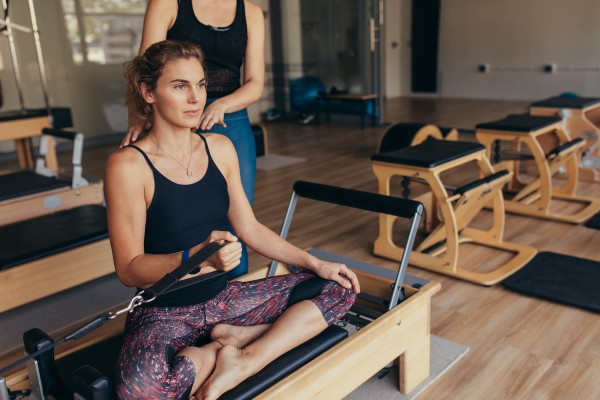 Fitness women sitting with legs crossed on a pilates training machine and pulling the stretch band. Pilates trainer guiding a woman at the gym doing strength training.